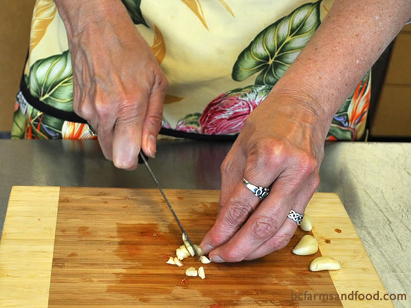 Chop garlic and fresh basil (or other herbs) and add them to the tomatoes.