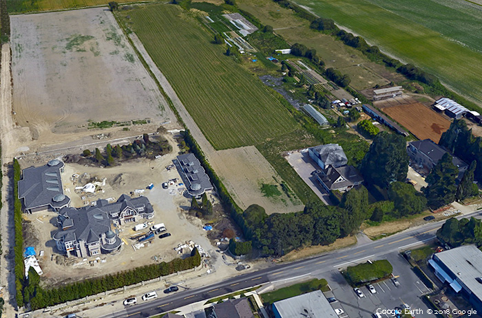 A large mansion under construction sits on unused farmland adjacent to an active farm in Richmond, BC. Why Farmland Protection is Not Enough.
