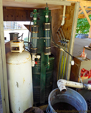 Tanks and a digestate collection bucket which make up part of the anaerobic digester at the farm. A Low-Carbon Citrus Fruit Greenhouse in Canada.