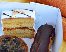 A gluten-free tart, slice of cake, and eclair boxed to go from Origin Bakery.