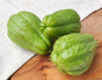 Three bright green spiny pear-shaped chayote squash on a cutting board. Sauteed Chayote Squash Recipe.