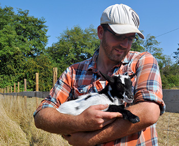 Chris Margetts holds a baby goat at The Fickle Fig Farm.