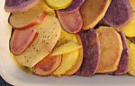 Colourful Scalloped Potatoes recipe. Sliced red, yellow and blue potatoes in a baking dish.