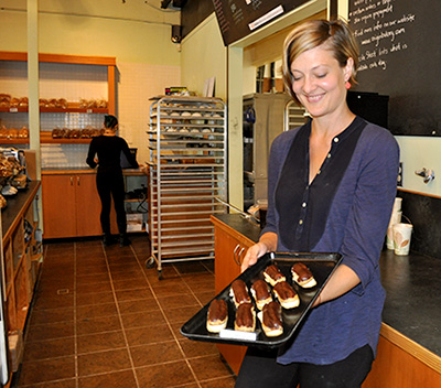 Marion Scott holds a tray of gluten-free eclairs made at Origin Bakery.