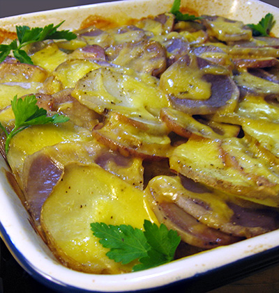 Scalloped potatoes prepared with red, blue and yellow potatoes. Topped with cheddar cheese. Colourful Scalloped Potatoes recipe.